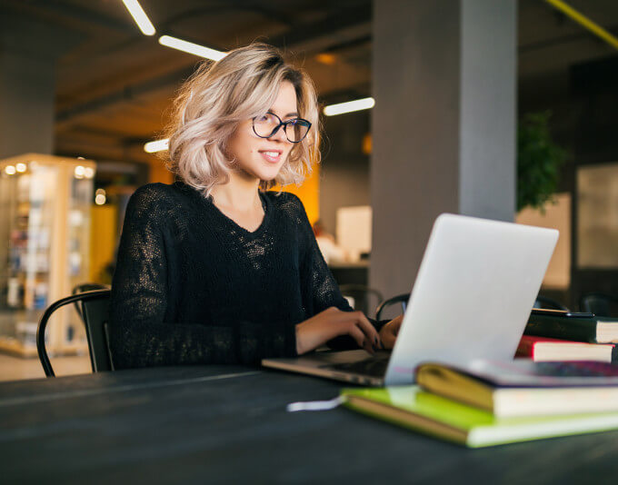 portrait young pretty smiling woman sitting table black shirt working laptop co working office wearing glasses
